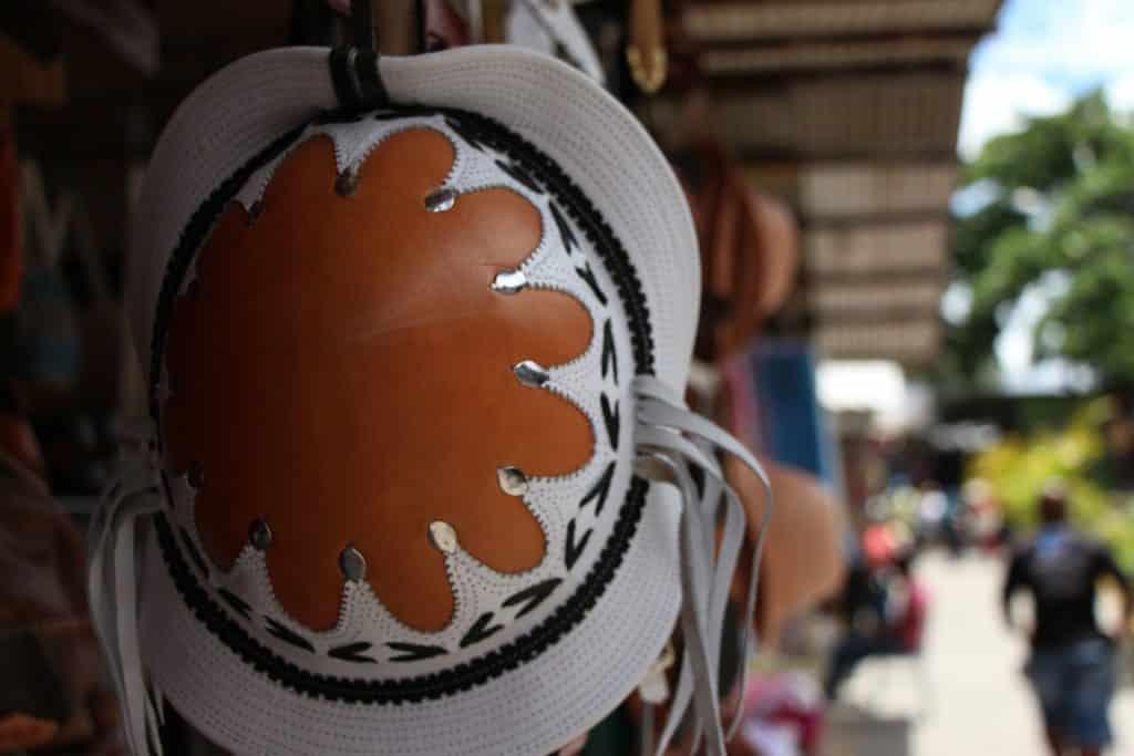 Imagem do tradicional chapéu nordestino pendurado em uma barraca no centro de uma cidade do nordeste.