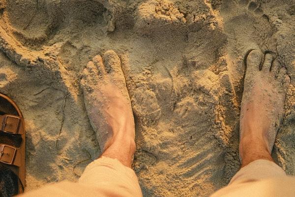 Pés descalços na areia vistos de cima