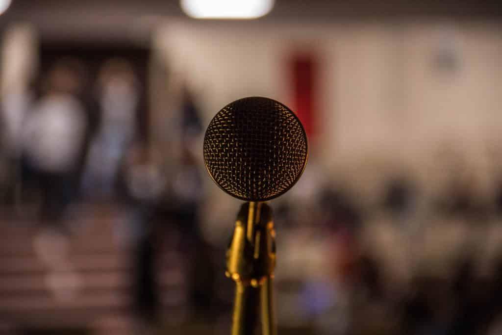 Microfone em um palco com pessoas no fundo