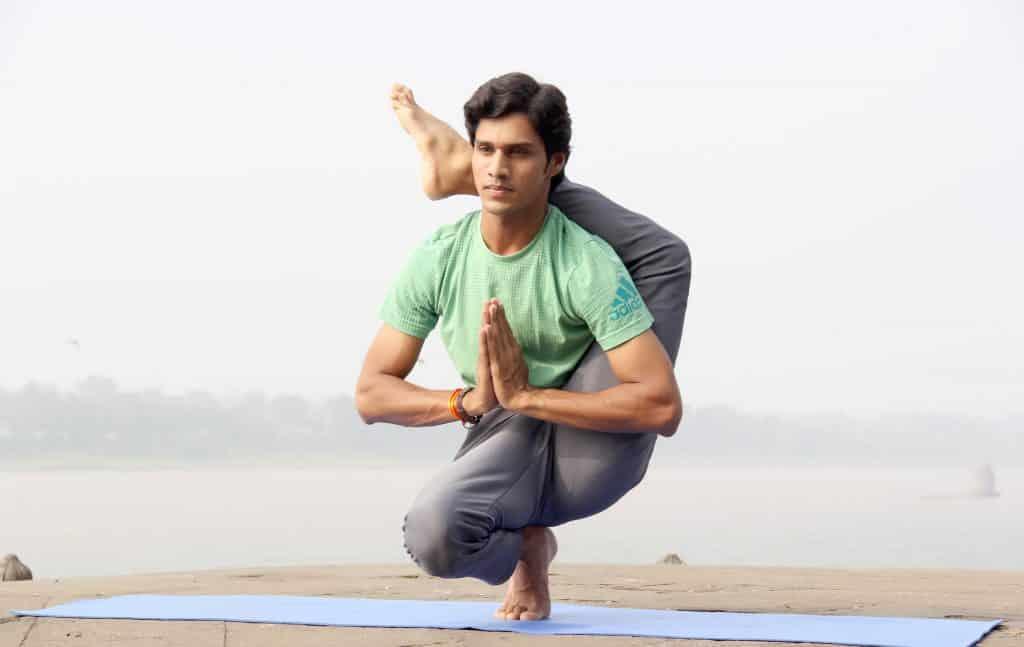 Homem fazendo uma pose de Yoga em um tapete azul.