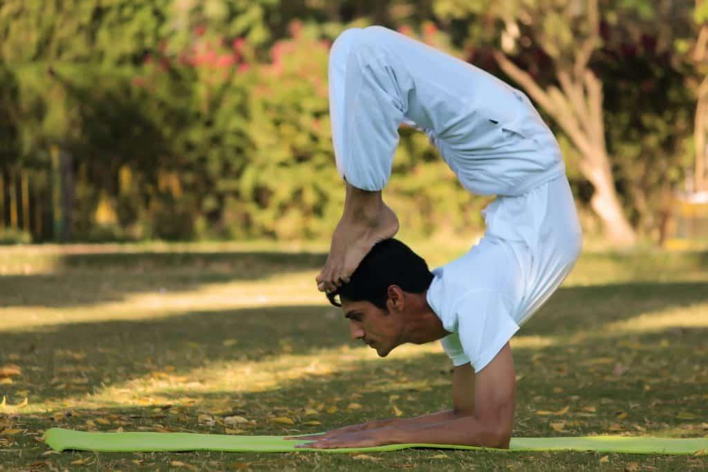 Homem fazendo Yoga em um parque.