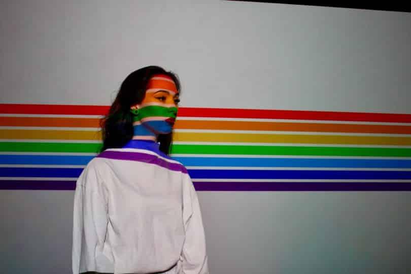 Mulher ao lado de uma parede que está refletindo as cores do arco íris