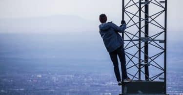 Pessoa se segurando em uma torre olhando para o mar um