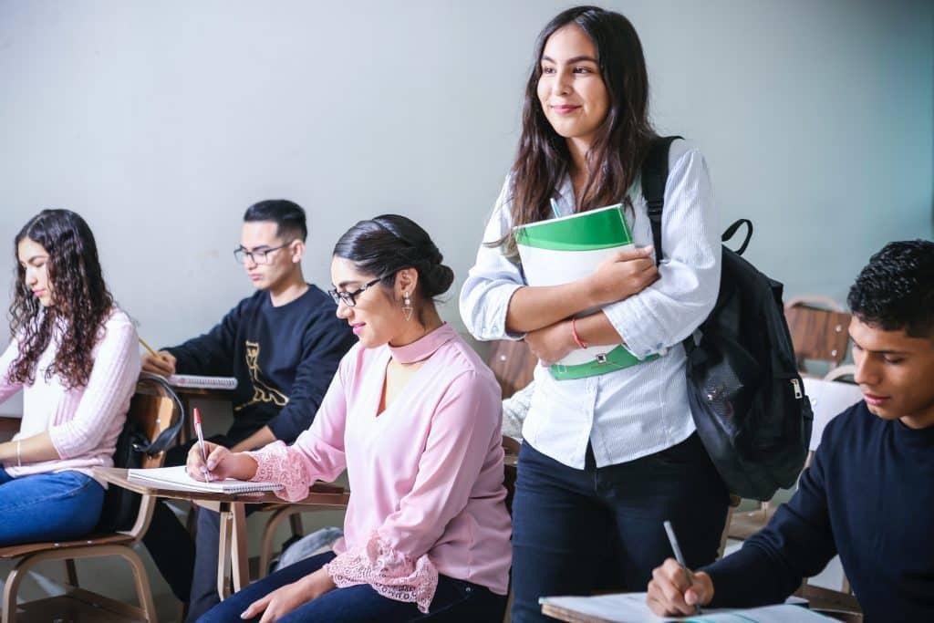 Aluna em pé na sala de aula segurando seus livros e sorrindo