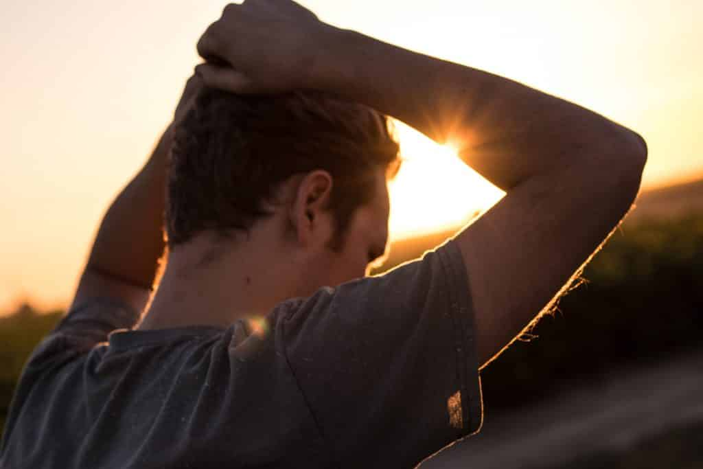 Homem com suas mãos na cabeça em direção ao pôr do sol
