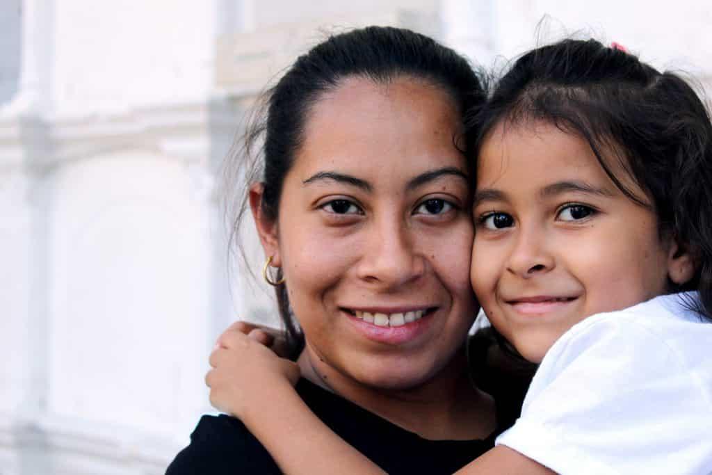 Mãe e filha abraçadas olhando para a câmera.