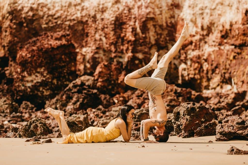 Homem em posição de yoga enquanto a namorada está olhando pra ele.