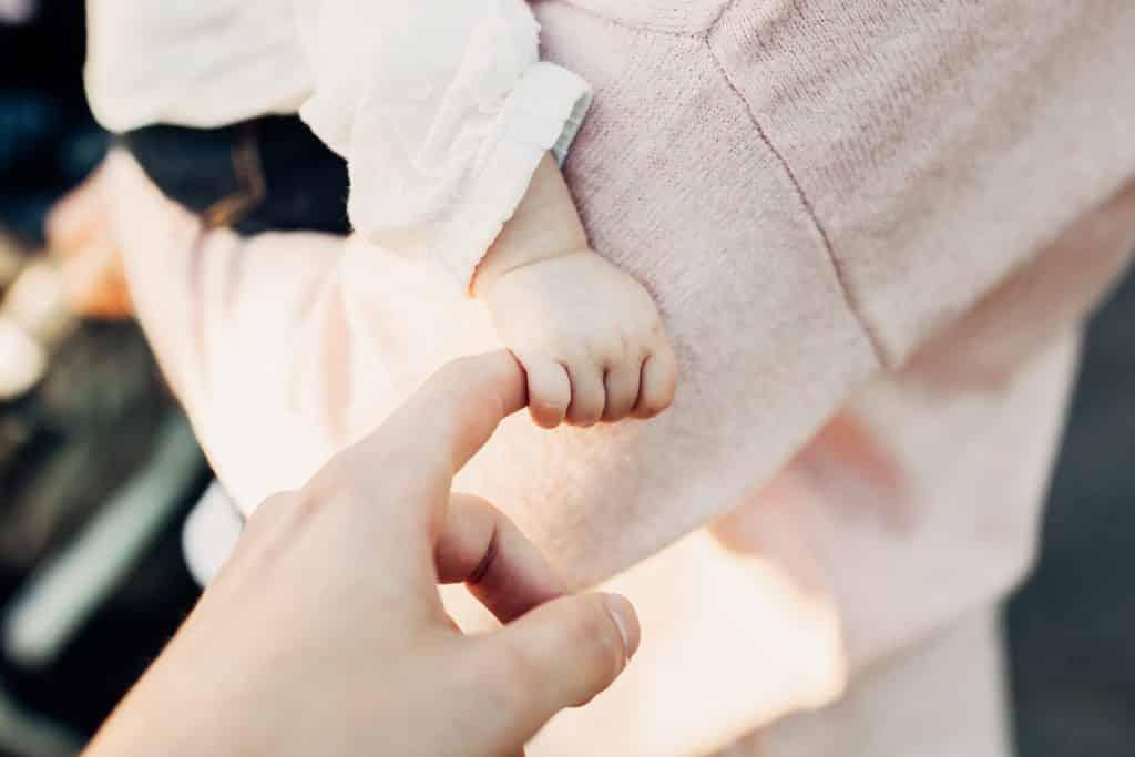 Bebê segurando com sua mãozinha o dedo de sua mãe