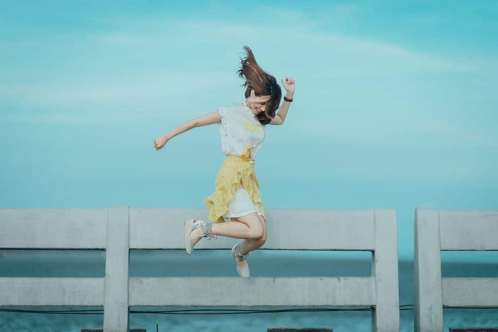 Mulher pulando em frente ao mar, mexendo os braços.