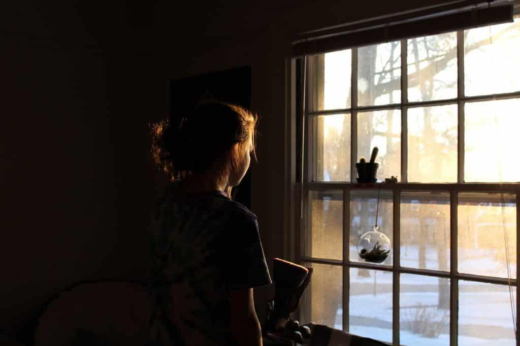 Mulher pensativa olhando para fora da janela