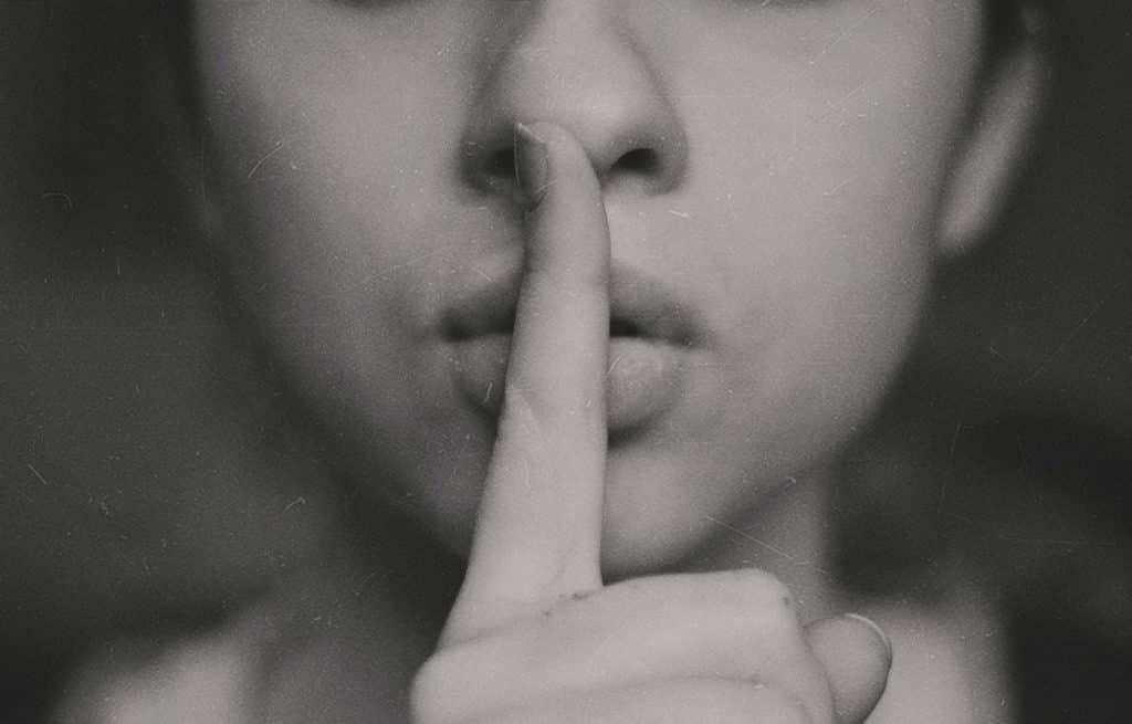 Rosto de mulher, exibindo apenas abaixo dos olhos, com um dedo indicador na frente dos lábios, indicando silêncio