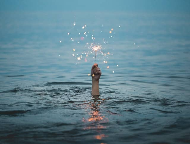 Mão saindo da água segurando vela de brilho
