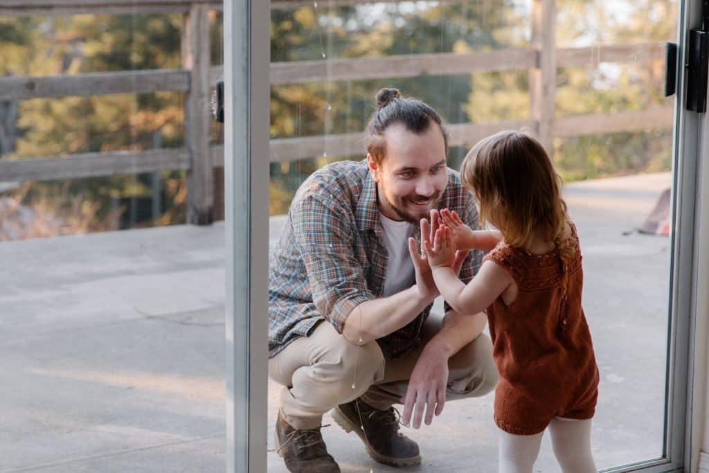 Homem agachado em frente a uma porta de vidro, juntando as mãos com sua filha pequena do outro lado.