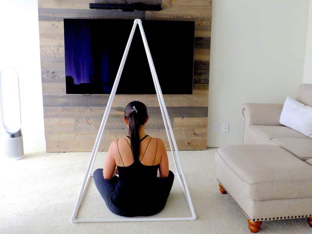Mulher sentada no chão da sala de estar, meditando sob uma pirâmide metálica.