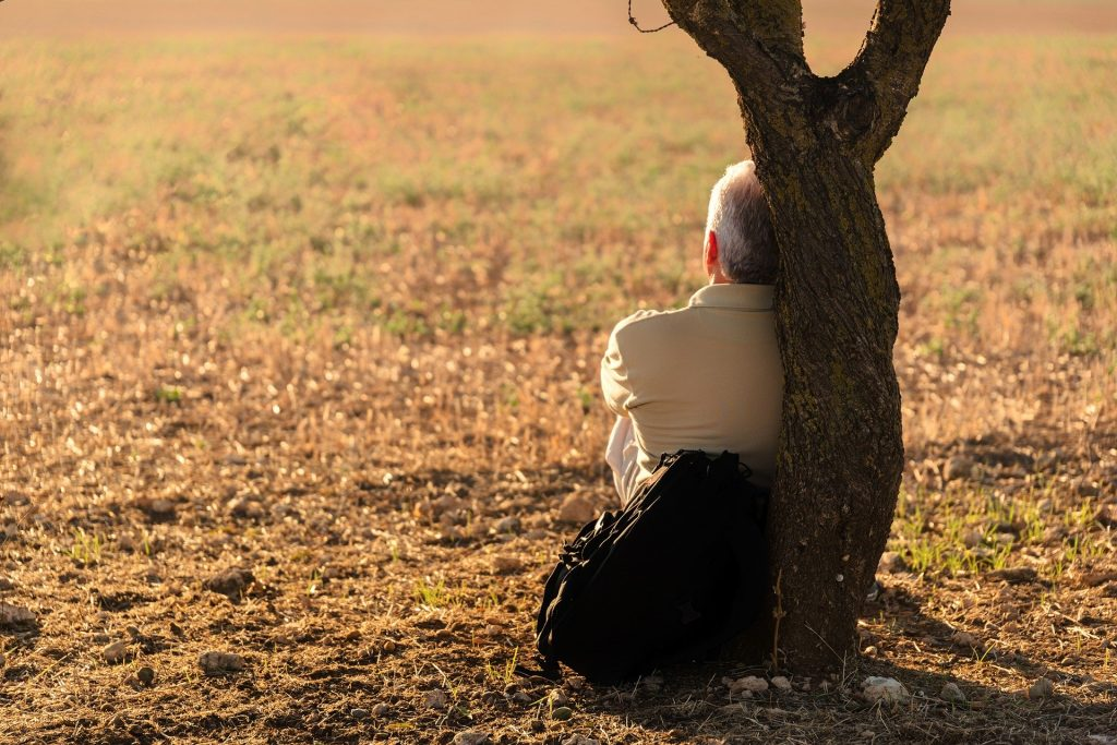 Imagem de um homem de meia idade sentado e encostado em um tronco de árvore. Ele veste uma jaqueta bege e ao lado dele uma mochila preta.