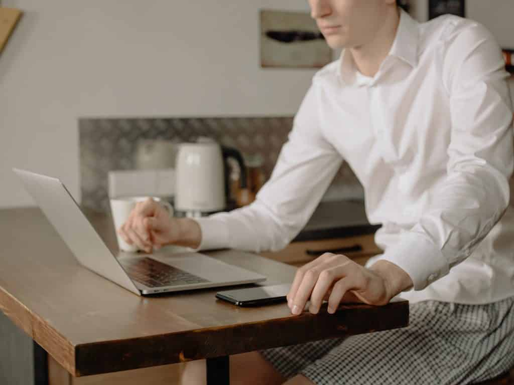 Homem sentado na mesa da cozinha, trabalhando com seu computador.