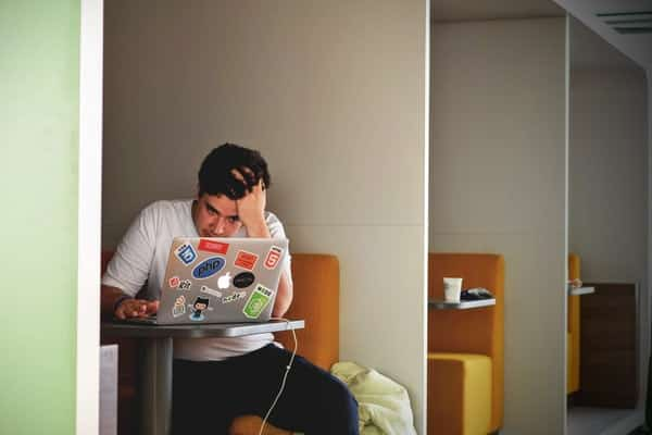 Homem mexendo no computador com mão na cabeça preocupado