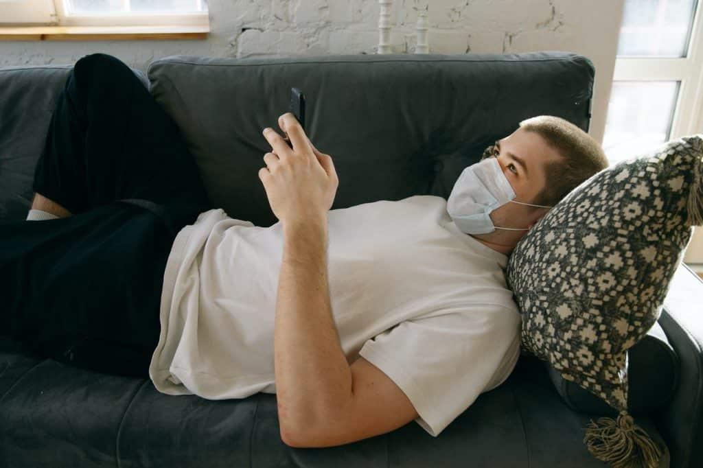Homem deitado em sofá, usando máscara no rosto, e digitando em um celular.