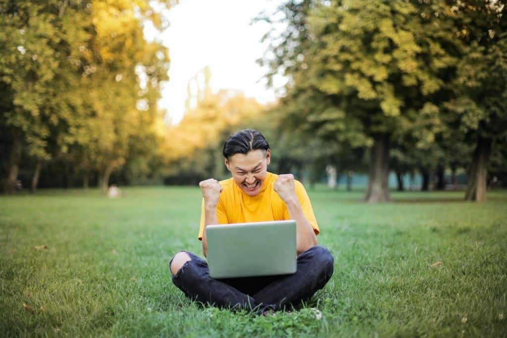 Homem sentado com as pernas cruzadas na grama e um notebook no colo. Ele está olhando para a tela, rindo, e com os punhos fechados na altura do rosto, celebrando algo.