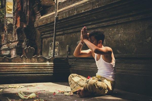 Homem meditando em templo de olhos fechados