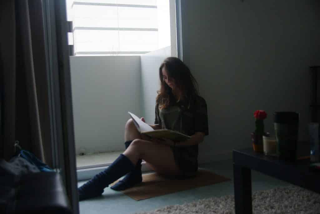Mulher sentada no chão da sala lendo um livro