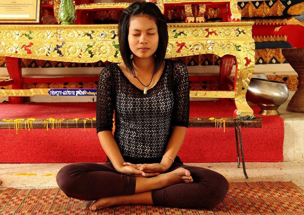 Mulher sentada em tapete com as pernas cruzadas, as mãos repousando em seus tornozelos e os olhos fechados.