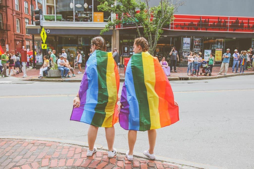 Duas mulheres na rua usando bandeira LGBT nas costas