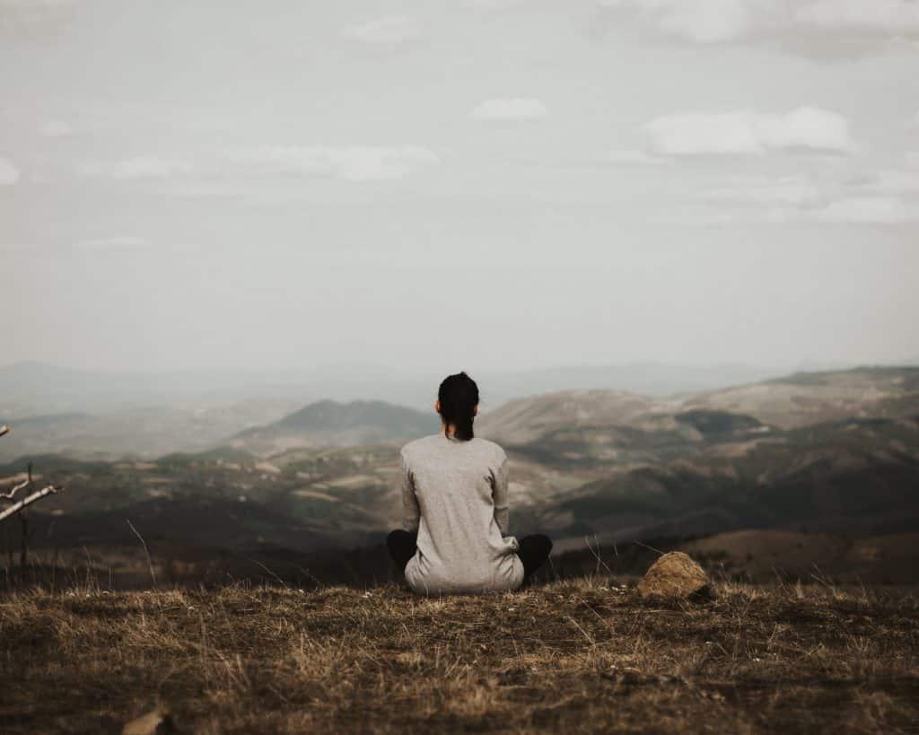 Mulher sentada em uma montanha observando ao seu redor outras montanhas