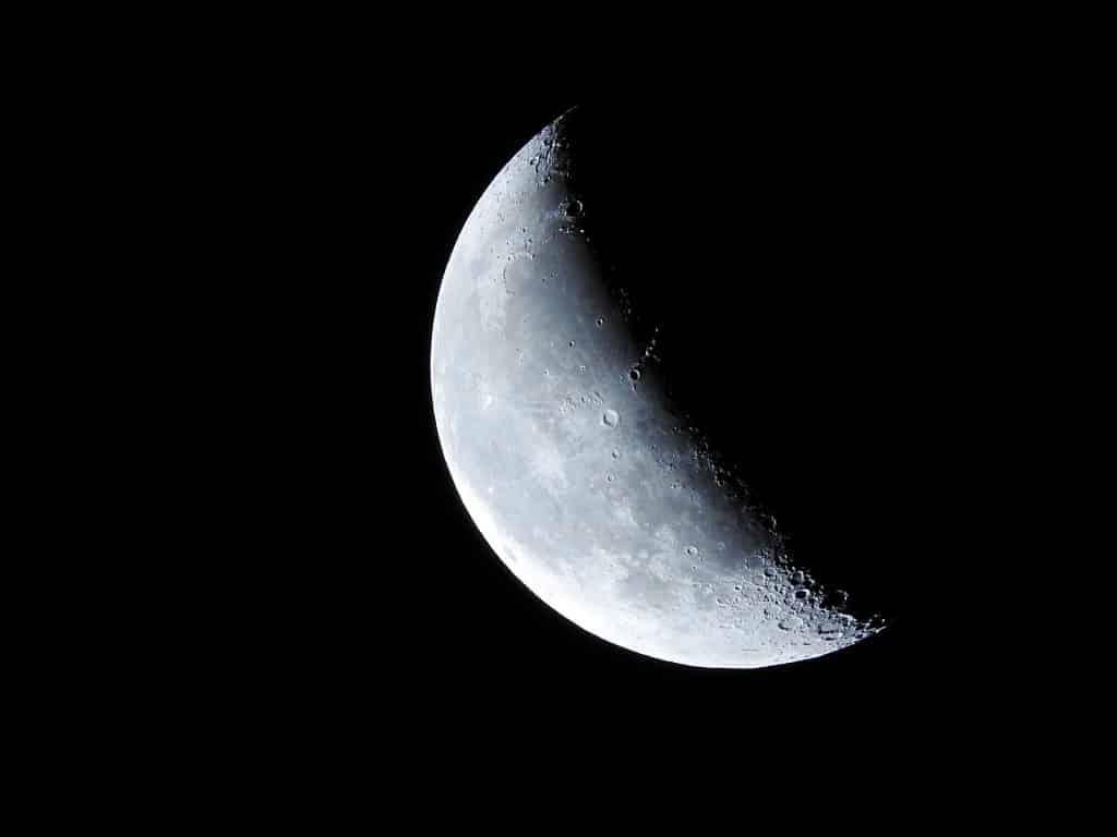 Imagem com fundo escuro e a lua crescente.