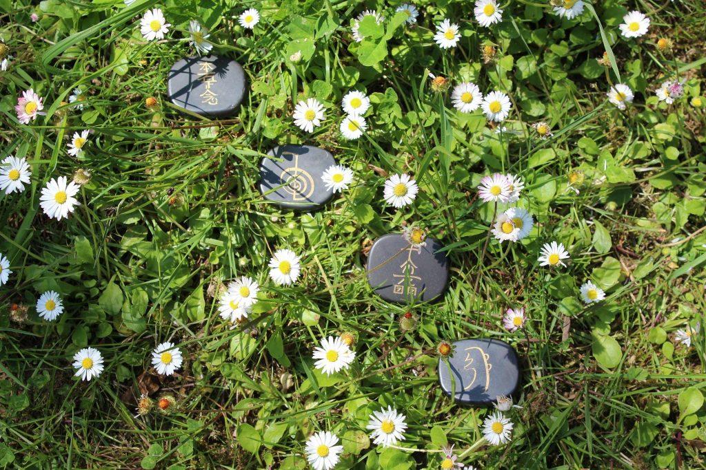 Flores (margaridas brancas) e pedras pintadas com desenhos orientais para o uso na aplicação do Reiki.