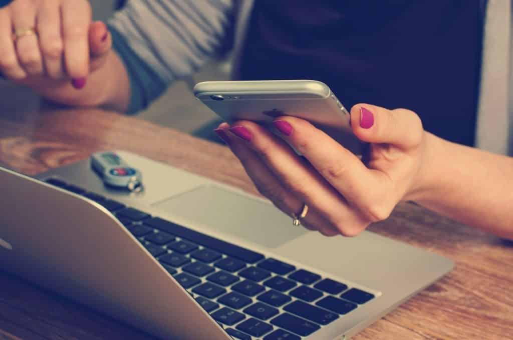 Mãos de mulher em frente a um notebook, e segurando um celular.