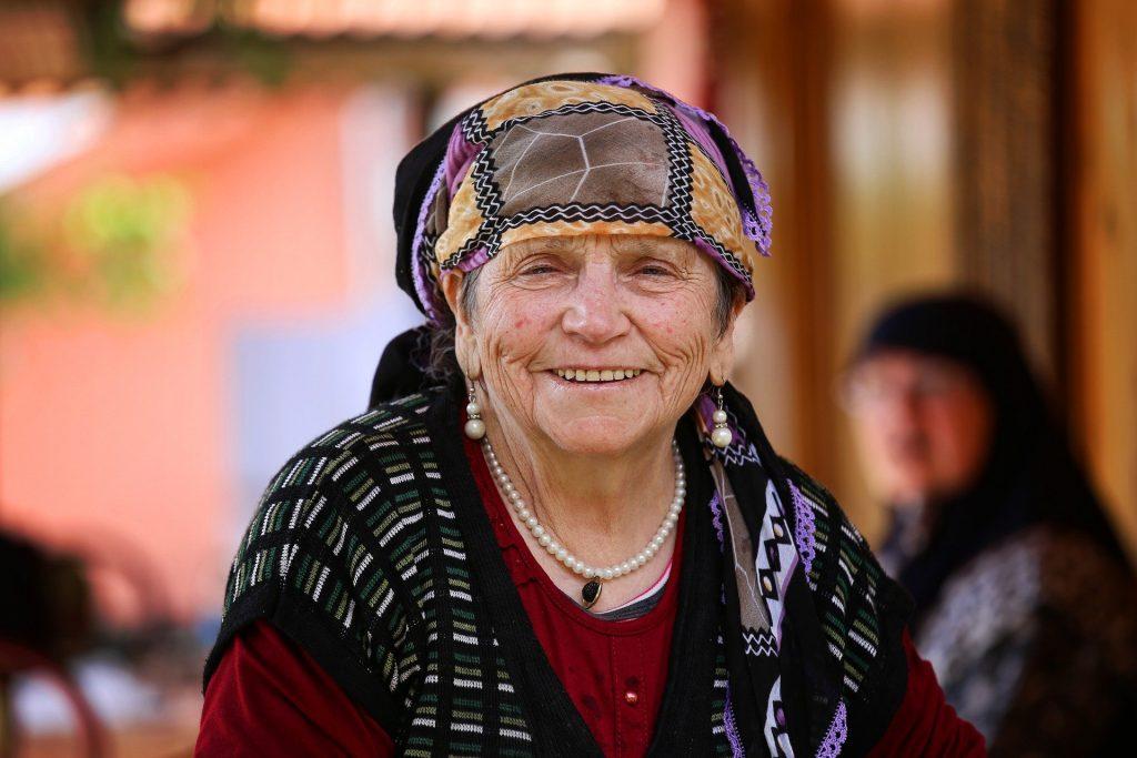Imagem do rosto de uma senhora idosa. Ela usa um lenço colorido sobre a cabeça e um lindo par de brincos de pérolas compridos.