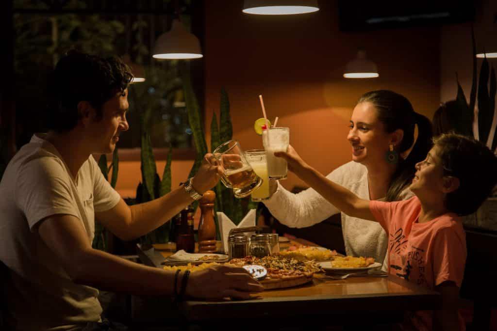 Família reunida na mesa comendo e brindando
