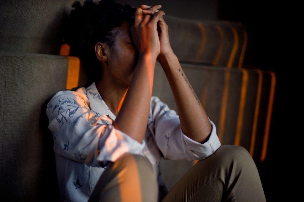 Mulher negra sozinha e triste. Alguém não foi grato a ela. Ela está sentada com as mãos no rosto,