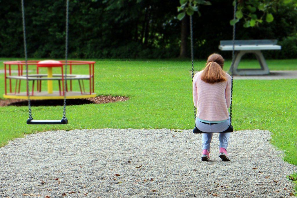 Mulher sozinha em um parque. Ela está triste, cabisbaixa e sentada em um balanço. Veste uma blusa e um tênis rosa e um calça jeans azul clara.