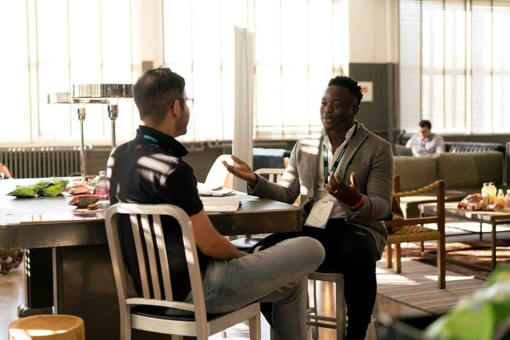 Dois homens com crachás de empresa sentados em uma mesa, conversando.