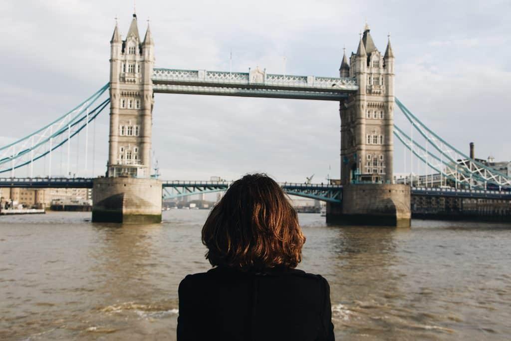 Mulher de costas em frente à London Bridge,em Londres.