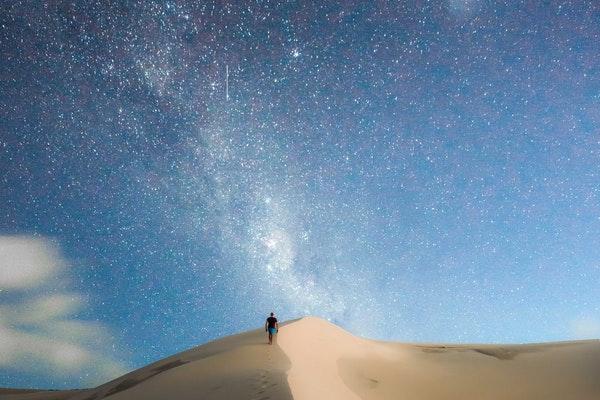 Homem caminhando em deserto de areia com céu azul estrelado