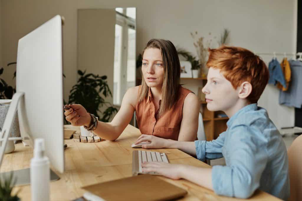 Mulher ajudando seu filho a usar o computador durante a quarentena.