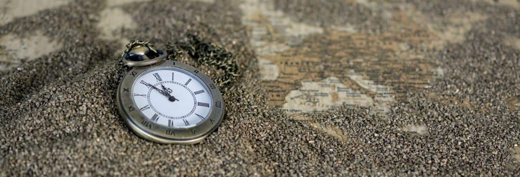Imagem de um relógio de bolso na cor dourado velho, Ele está sobre uma mesa forrada com grãos de metal e um mapa antigo,