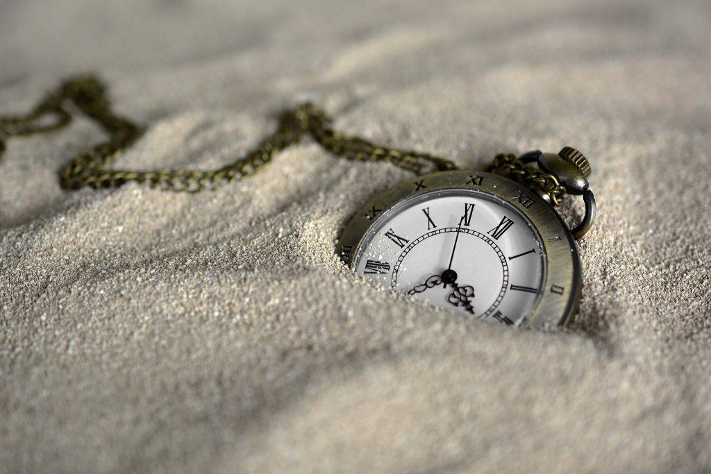 Imagem de um relógio de bolso com cordinha. Ele está sobre  uma areia.