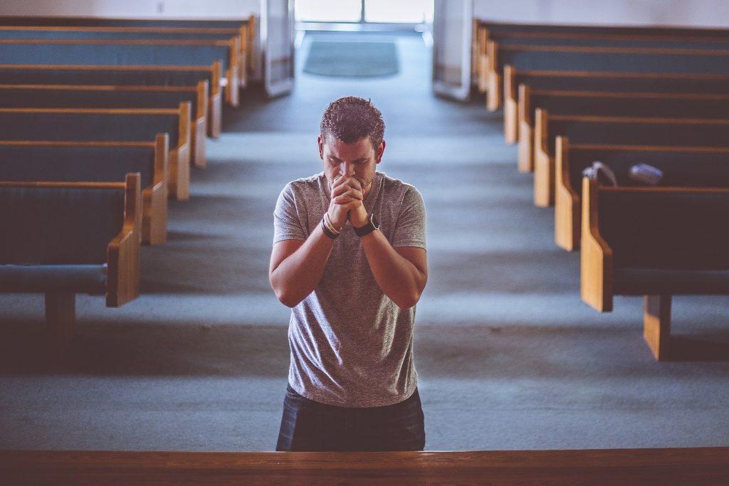 Homem dentro de um templo religioso. Ele está de joelhos orando e com os olhos fechados.