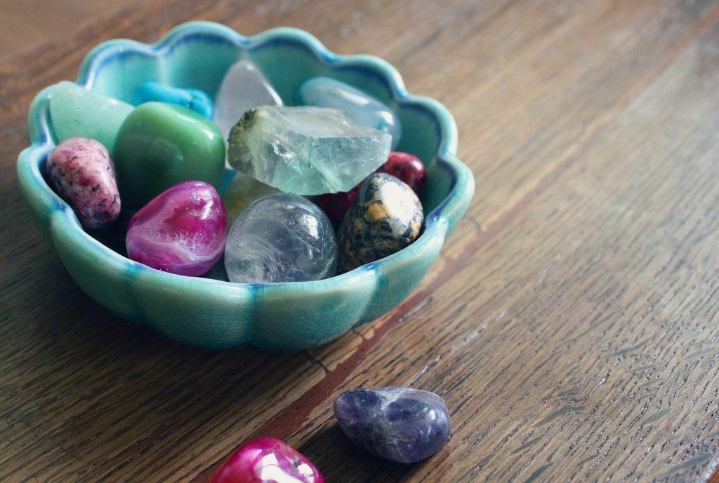 Imagem de um pote pequeno de porcelana na cor azul claro. Dentro dele vários tipos de predas preciosas para uso em terapia.