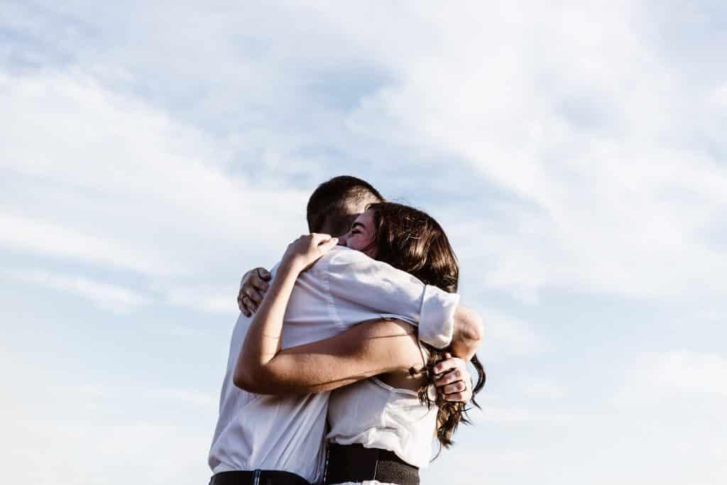 Homem e mulher se abraçando em um local aberto