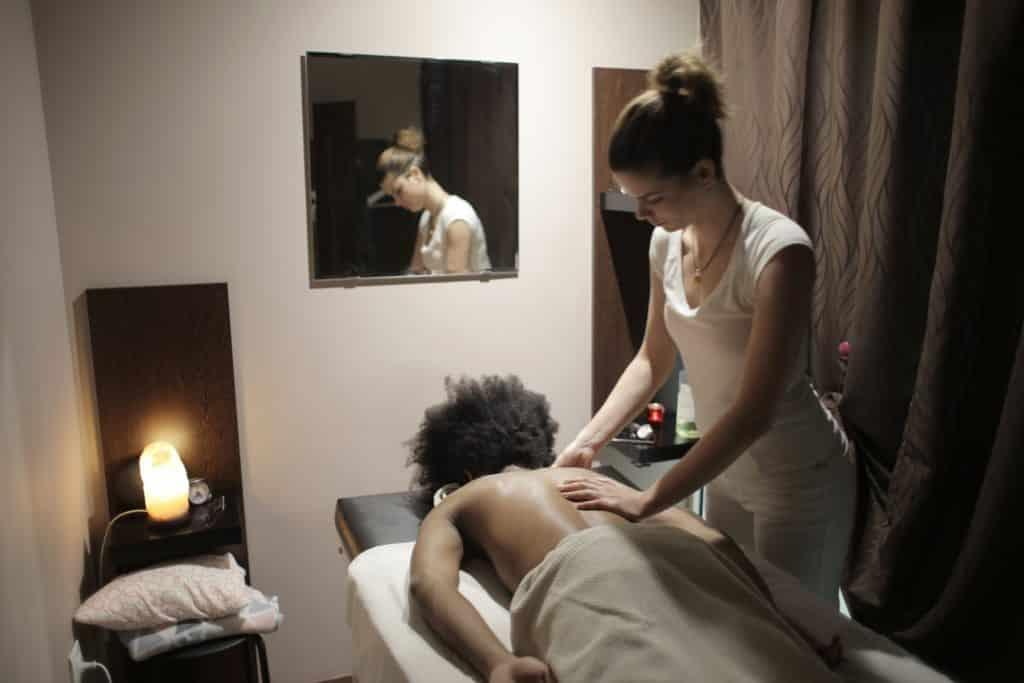Mulher massageando pessoa deitada nas costas, em ambiente calmo à luz de velas.