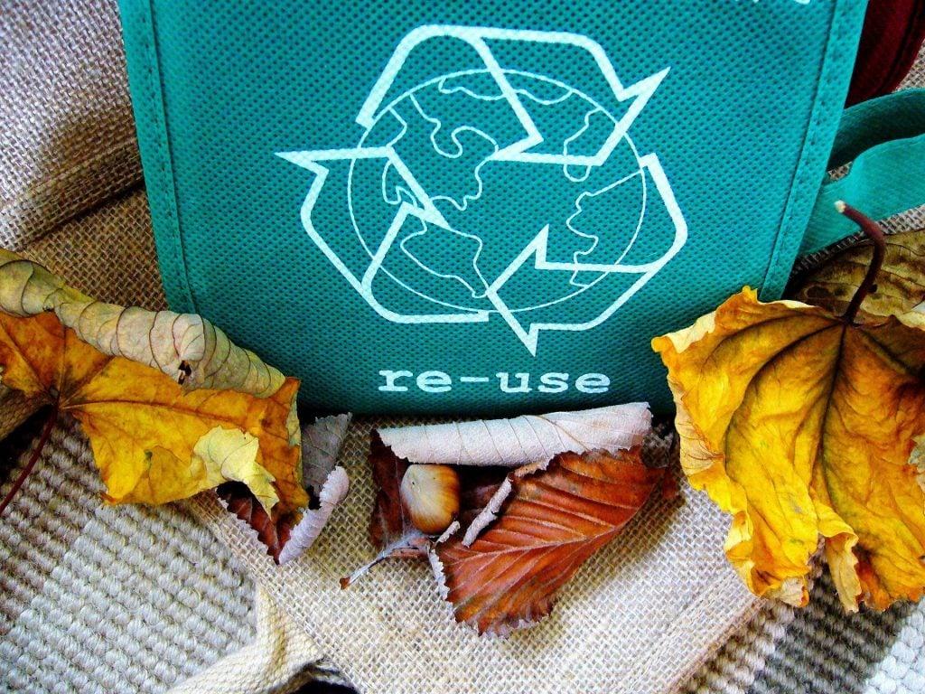 Imagem de vários tecidos rústicos e de várias cores e modelos. Em um deles de cor azul, está o símbolo da reciclagem desenhado em branco e a palacra re-use escrita também em branco.