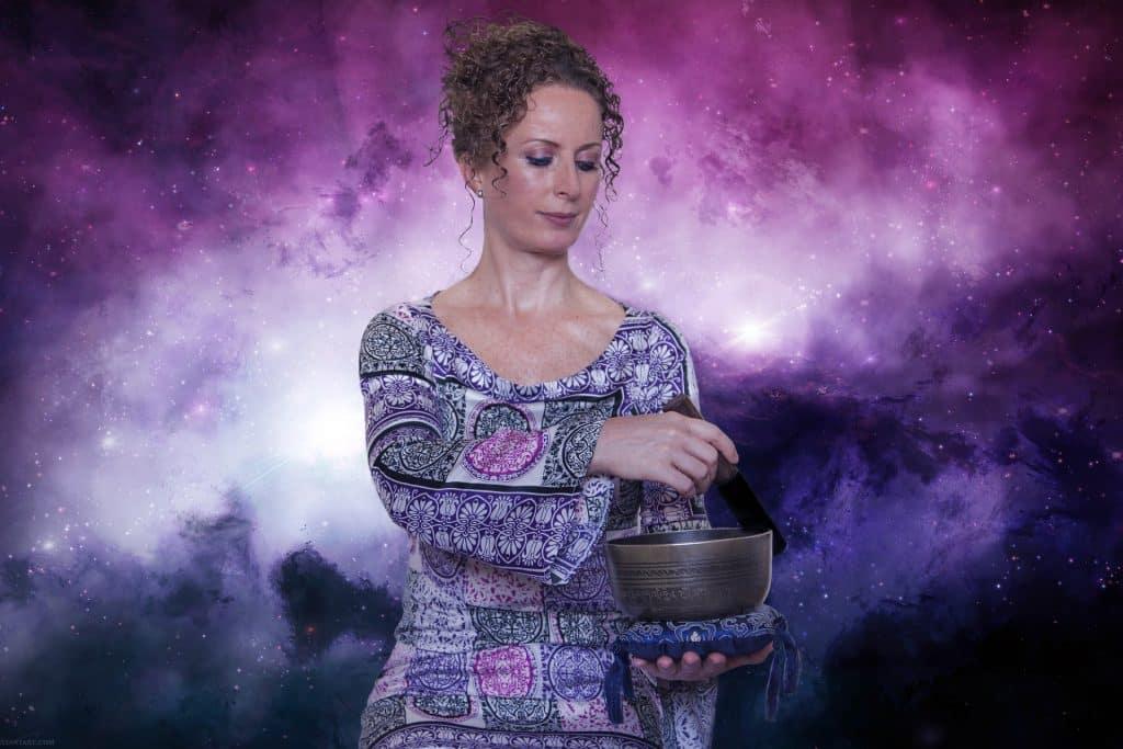 Mulher preparando uma base para o uso durante a aplicação do Reiki. Ela usa um vestido com desenhos abstratos. Ao fundo um painel parecendo a imagem do universo nas cores roxo, lilás e branco.