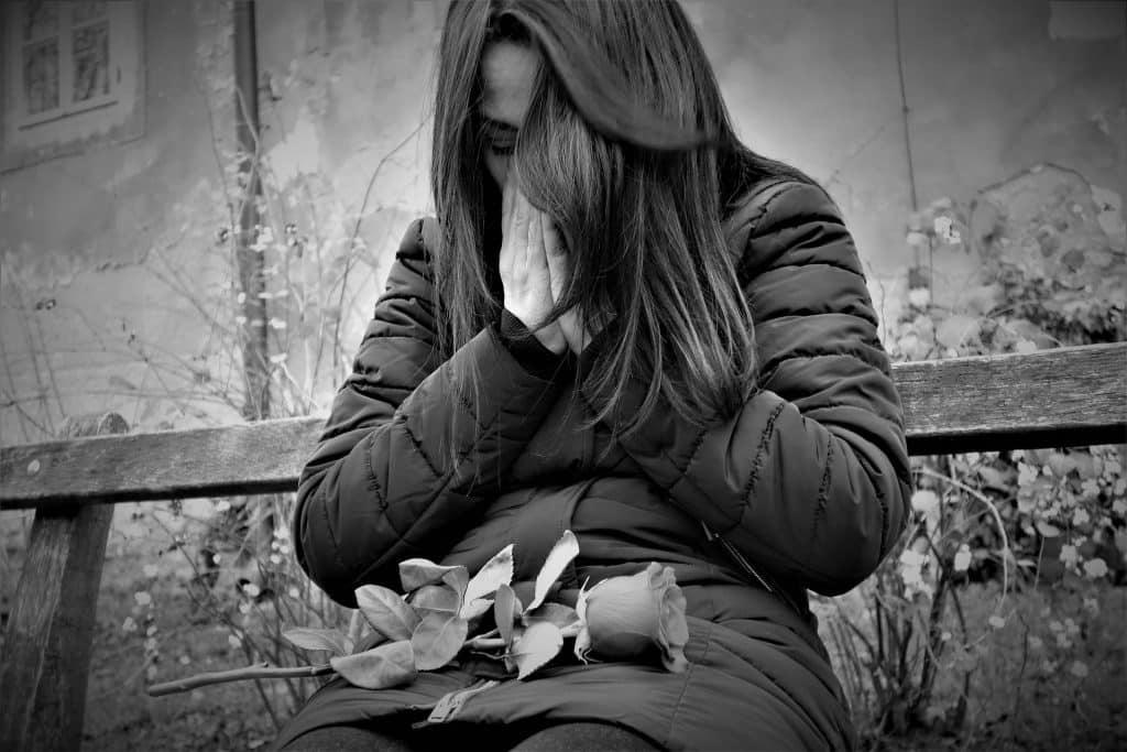 Imagem em preto e branco de uma jovem mulher de cabelos longos sentada em um banco de mandeira. Ela está chorando e sobre o seu colo uma rosa.