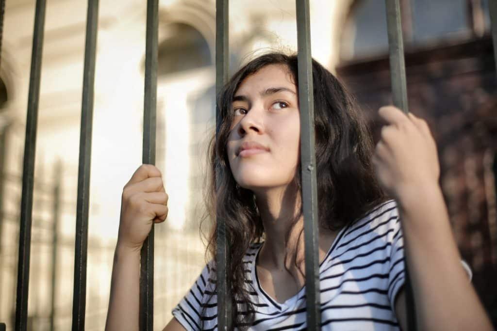 Mulher jovem de cabelos ondulados olhando pelas grades de uma construção.