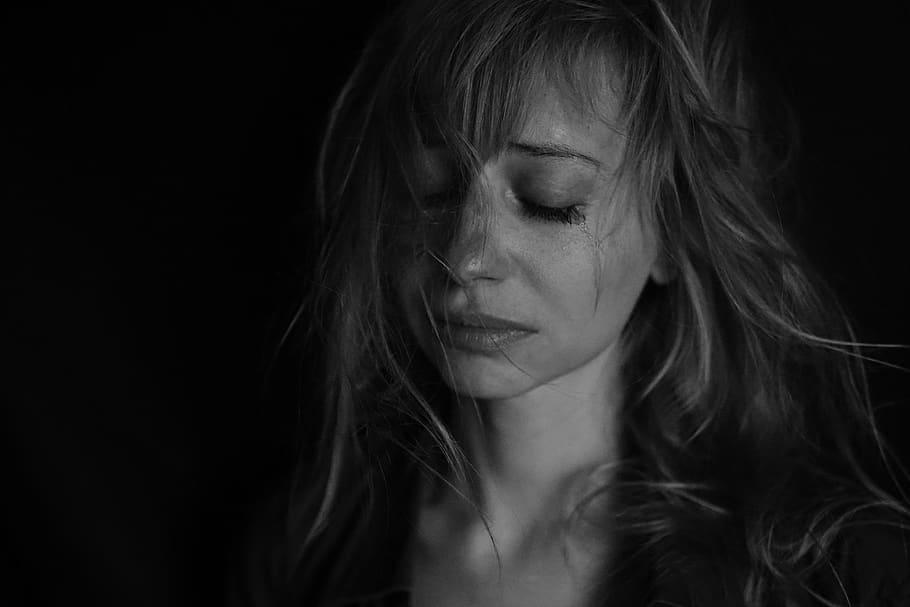 Mulher jovem chorando, com os olhos fechados e mechas de seu cabelo grudadas no rosto.
